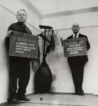 "John Heartfield and Wieland Herzfelde perform ""In Memoriam Pop Art, this miscarriage of grandmother Dada"" at Heartfield's exhibition ""Stále jestj"" (Still), Prague, 1964. Photo: Akademie der Künste, Berlin, JHA 596/12.5.2."
